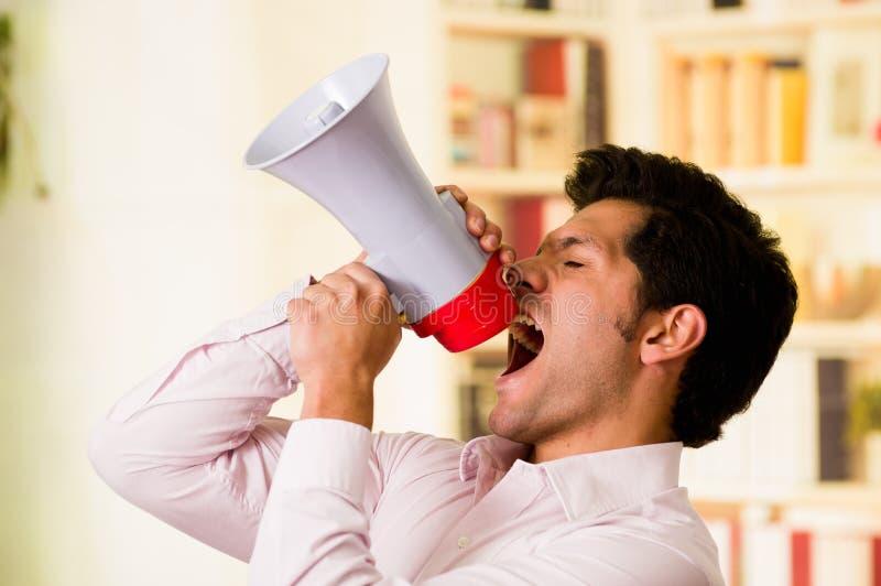 Портрет красивого человека крича с мегафоном пока он держит с обеими руками запачканный мегафон в стоковые фотографии rf