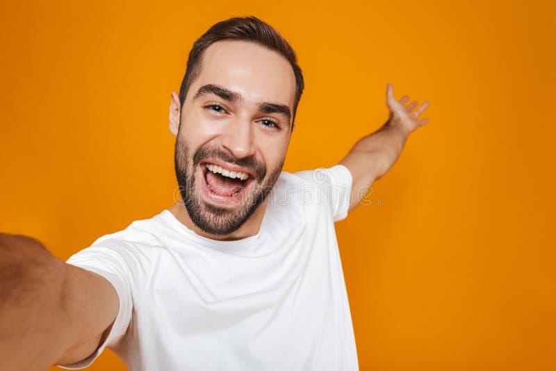 Портрет красивого человека 30s в футболке усмехаясь пока принимающ фото selfie, над желтой предпосылкой стоковое изображение rf