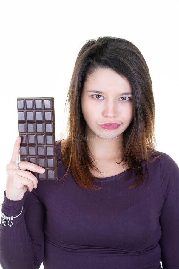 Портрет красивого шоколадного батончика удерживания молодой женщины  стоковое фото