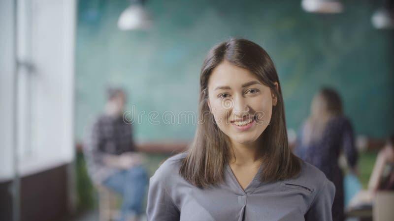 Портрет красивой азиатской женщины в современном офисе Молодая успешная коммерсантка смотря камеру, усмехаясь стоковое изображение