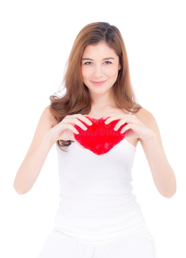 Портрет красивой азиатской молодой женщины держа красную подушку и улыбку формы сердца изолированный на белой предпосылке стоковая фотография rf