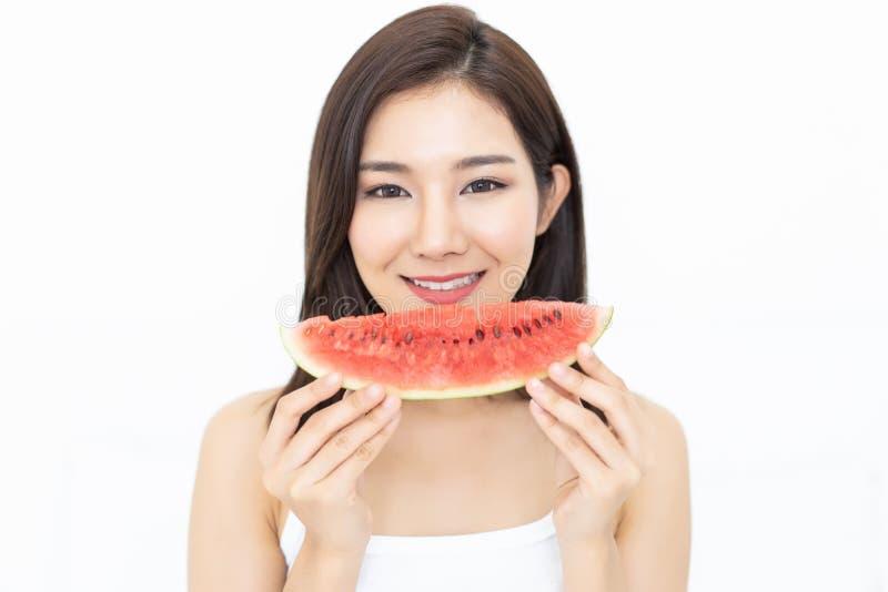 Портрет красивой азиатской молодой женщины есть арбуз на w стоковая фотография