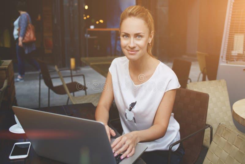 Портрет красивой дамы сидя на таблице кафа тротуара с открытым портативным компьютером стоковое изображение