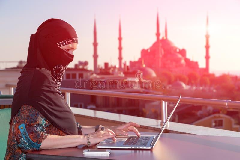 Портрет красивой аравийской женщины работая на компьютере стоковые фото