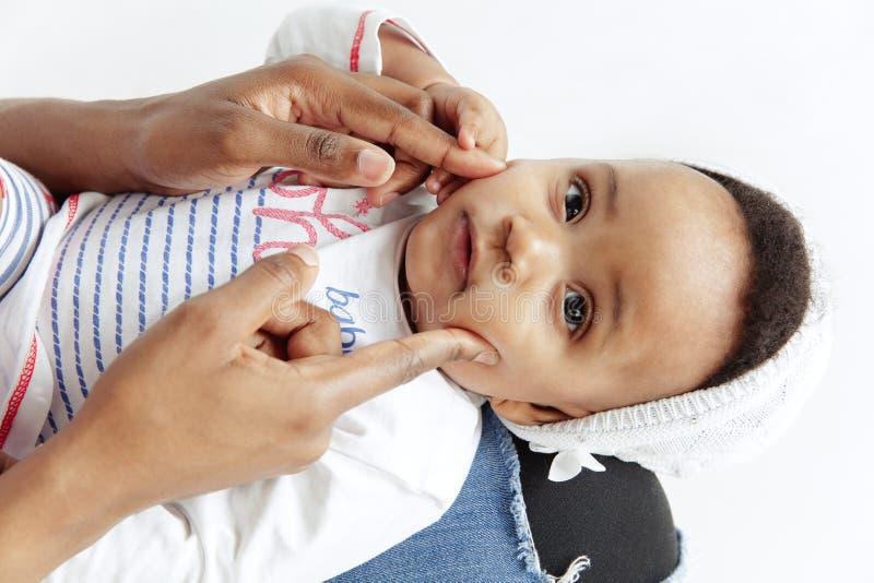 Портрет красивой африканской женщины держа на руках ее меньшего младенца стоковые фото