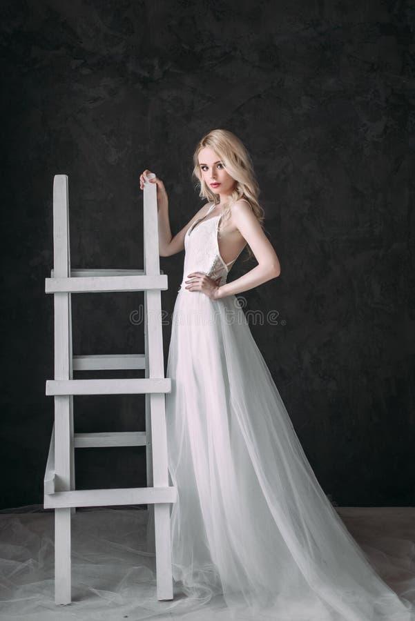 Портрет красивой белокурой девушки в изображении невесты Сторона красотки Фото сняло в студии на серой предпосылке стоковые фото