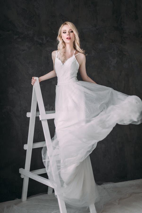 Портрет красивой белокурой девушки в изображении невесты Сторона красотки Фото сняло в студии на серой предпосылке стоковое изображение