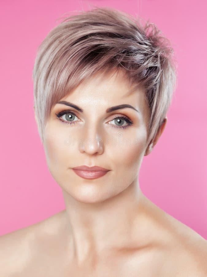 Портрет красивой белокурой женщины с красивым макияжем и короткой стрижкой после красить волосы в салоне парикмахерских услуг стоковое изображение