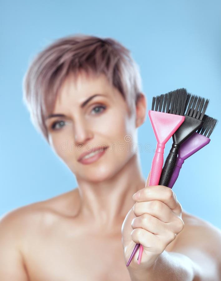 Портрет красивой белокурой женщины с красивым макияжем и короткой стрижки после красить волосы держит в щетке руки для красить стоковое фото