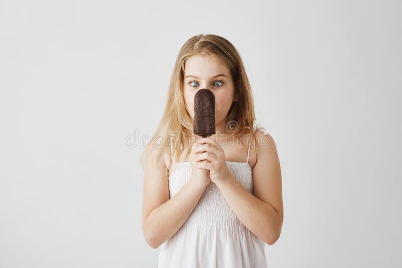 Портрет красивой белокурой маленькой девочки с представлять очаровательных голубых глазов придурковатый с мороженым в ее руках по стоковое изображение rf