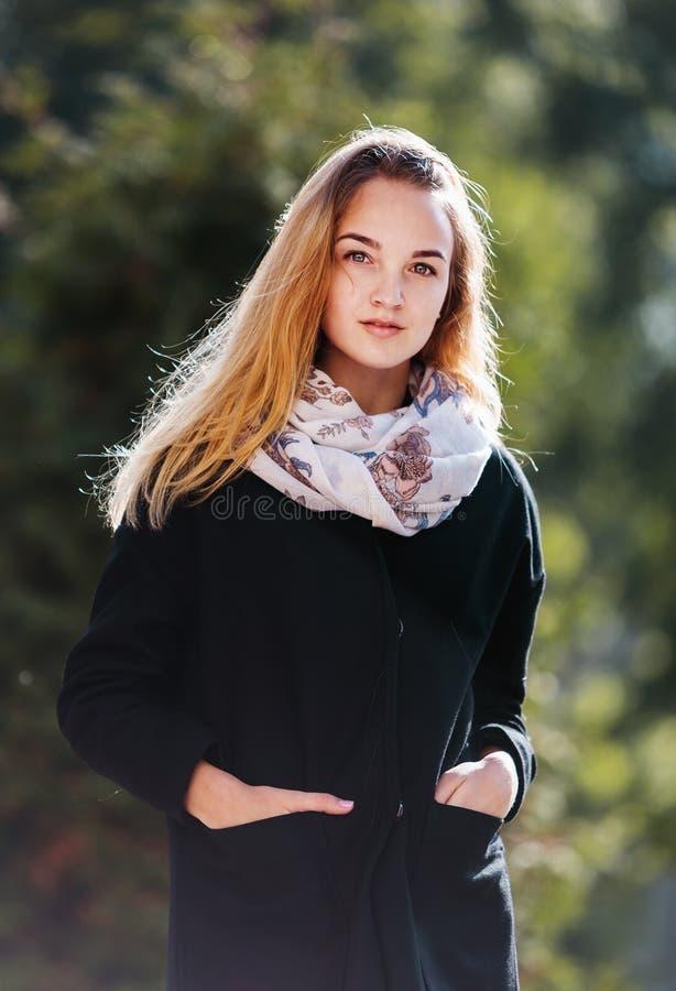 Портрет красивой белокурой девушки в черном пальто стоковые фотографии rf