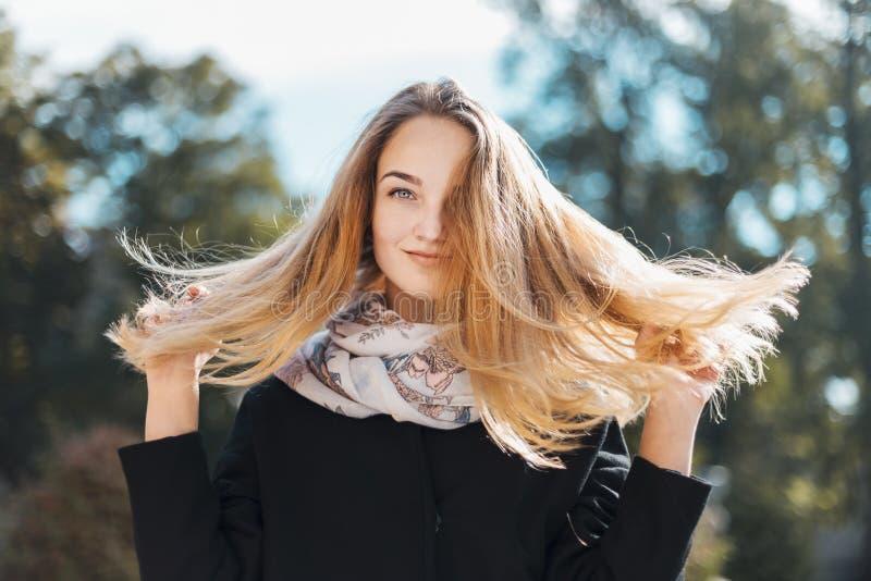 Портрет красивой белокурой девушки в черном пальто стоковые фото