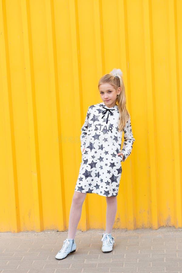 Портрет красивой белокурой девушки на желтой предпосылке стоковое изображение