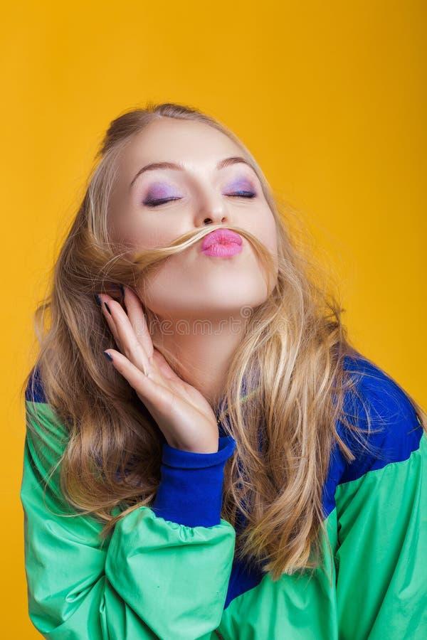 Портрет красивой белокурой женщины в вскользь красочных ярких одеждах делая усик с ее волосами стоковое фото rf