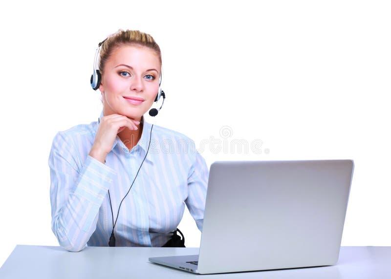 Портрет красивой бизнес-леди работая на ее столе с шлемофоном и компьтер-книжкой стоковые изображения rf