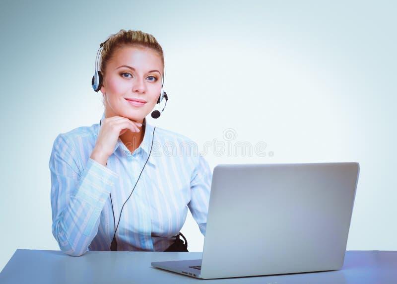Портрет красивой бизнес-леди работая на ее столе с шлемофоном и компьтер-книжкой стоковая фотография