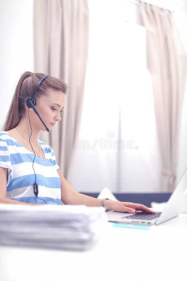 Портрет красивой бизнес-леди работая на ее столе со шлемофоном и ноутбуком стоковые фото