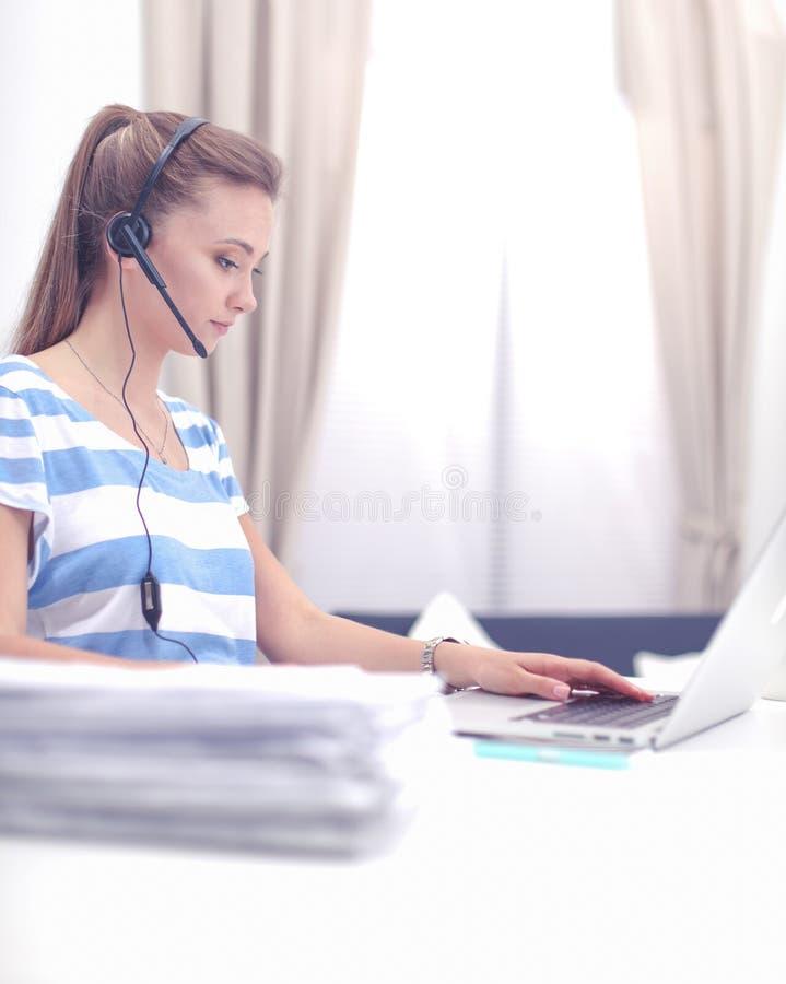 Портрет красивой бизнес-леди работая на ее столе со шлемофоном и ноутбуком стоковое изображение rf