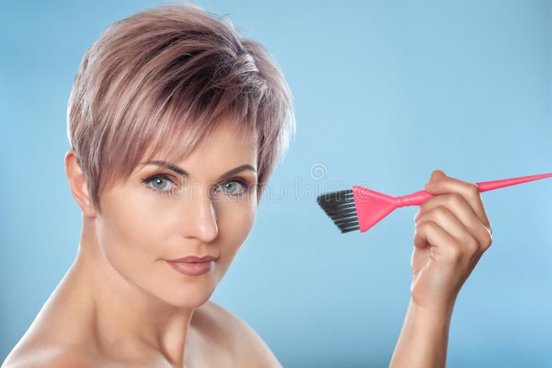 Портрет красивой блондинкы с красивыми макияжем и стрижками Kare для коротких волос держа щетку краски волос стоковое изображение rf