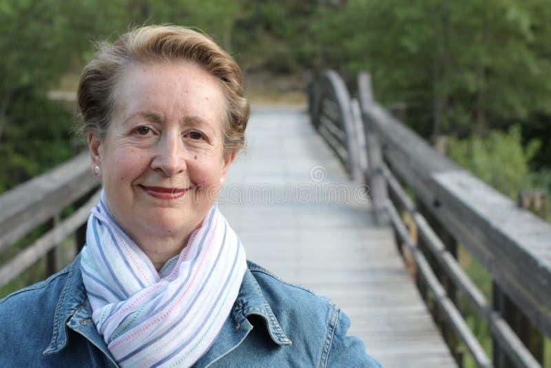 Портрет красивой более старой женщины усмехаясь в парке стоковые фотографии rf
