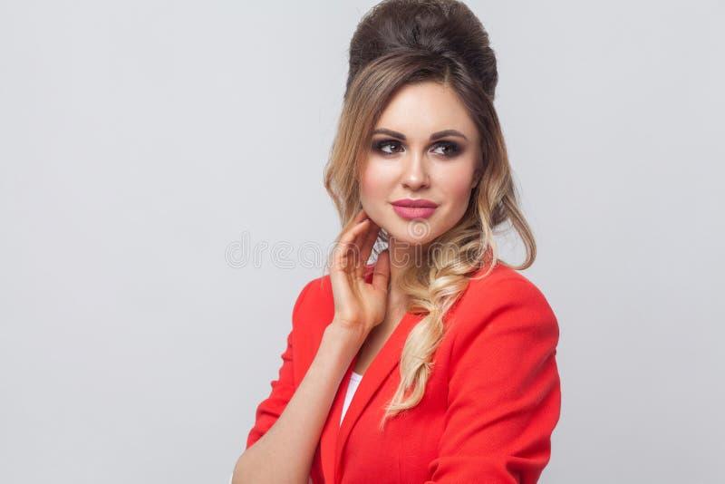 Портрет красивой дамы дела со стилем причесок и макияжем в красном причудливом положении блейзера, касающся ее стороне, смотря пр стоковое изображение rf
