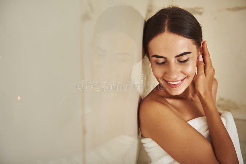 Портрет красивой дамы касаясь ее уху и усмехаться стоковое изображение rf
