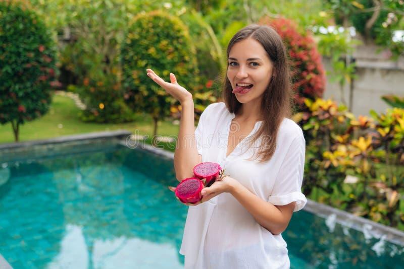 Портрет красивой девушки в белой рубашке с частями плода дракона в ее руках стоковая фотография rf