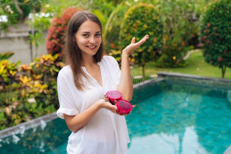 Портрет красивой девушки в белой рубашке с частями плода дракона в ее руках стоковые фотографии rf