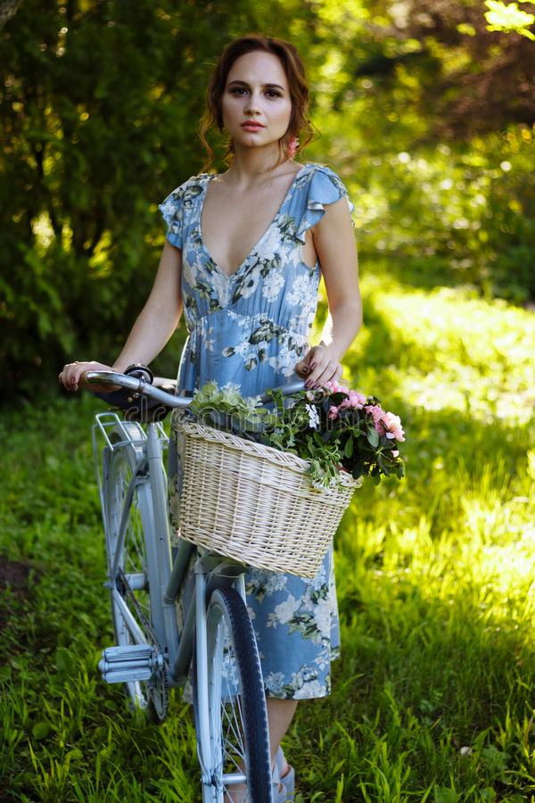 Портрет красивой девушки в лесе, держа велосипед с корзиной цветков, за лучами зацветенного солнца, голубое стоковое изображение rf