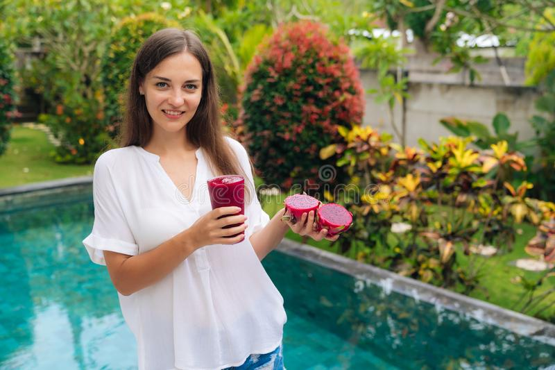 Портрет красивой девушки держит стекло smoothie плода дракона в ее руках около бассейна стоковые изображения rf
