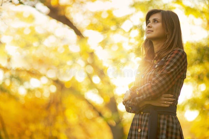 портрет красивой девушки идя в природу осенью, молодая женщина наслаждаясь солнечностью смотря вверх стоковая фотография rf