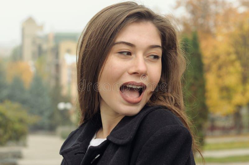 Портрет красивой девушки которая имеет потеху идя вдоль stree стоковое фото
