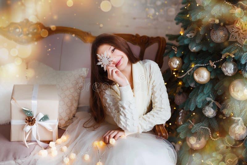 Портрет красивой девушки при длинные волосы нося теплую зиму одевает в интерьере рождества стоковое фото