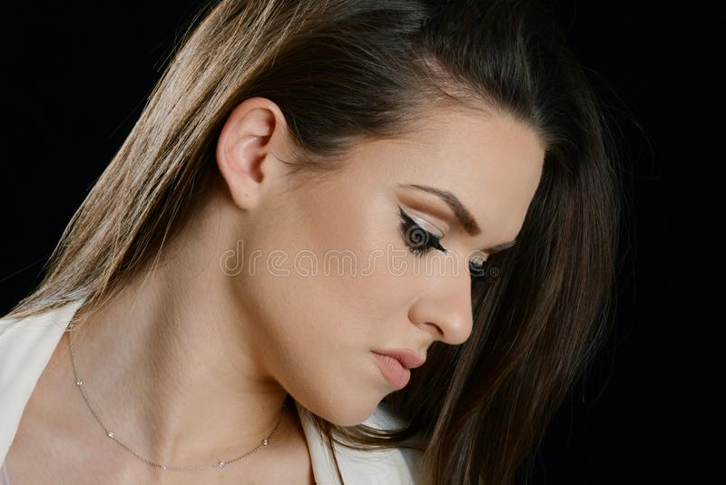 Портрет красивой девушки с длинными коричневыми волосами, смотря вниз стоковые изображения
