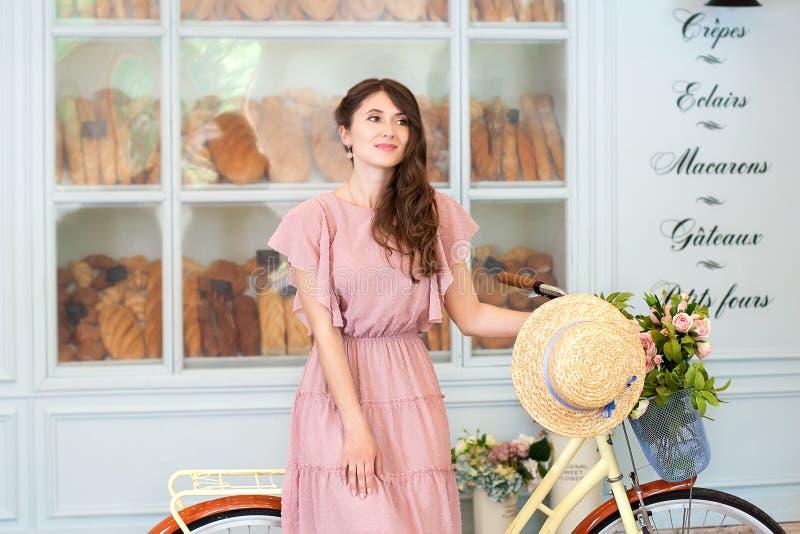 Портрет красивой девушки с длинным вьющиеся волосы в положении платья с желтым ретро велосипедом на предпосылке пекарни A стоковые фото