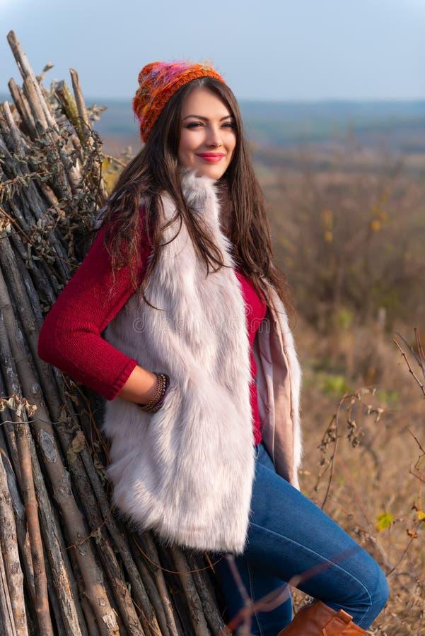 Портрет красивой девушки усмехаясь на камере, в стильных одеждах моды в пейзаже осени outdoors Шикарный стоковые фотографии rf