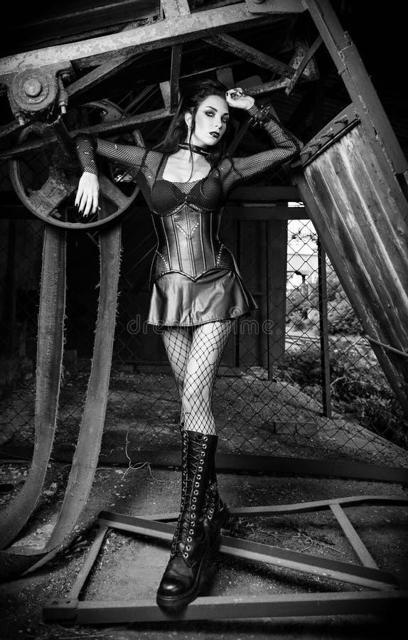 Портрет красивой девушки deathrock goth одел в пропускающей влагу блузке, юбке, корсете и ботинках стоя среди старых механизмов ч стоковое фото rf