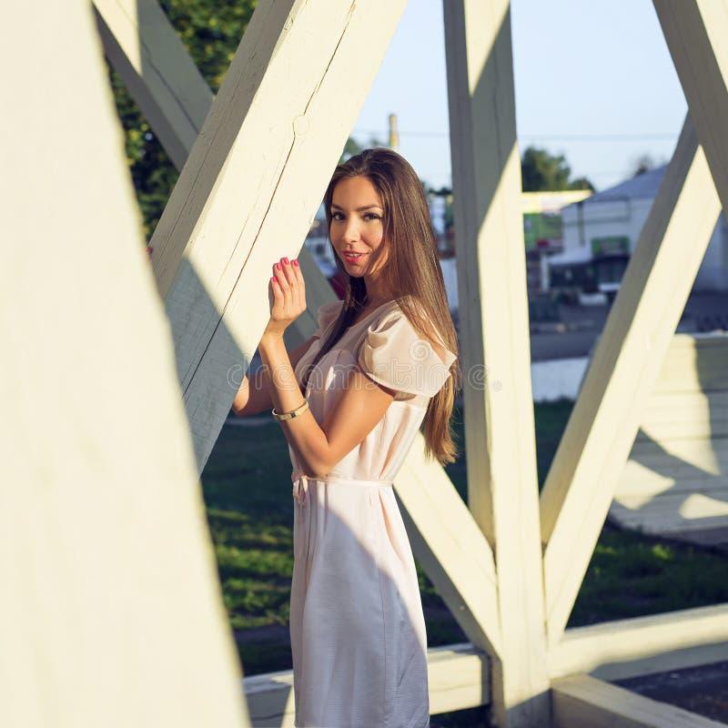 Портрет красивой девушки в платье стоя на деревянных штендерах отдыхая взгляд, стиль моды, городская жизнь, внутри стоковая фотография rf