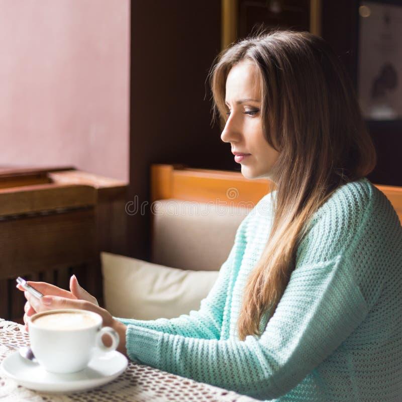 Портрет красивой девушки используя ее мобильный телефон в кафе стоковое изображение