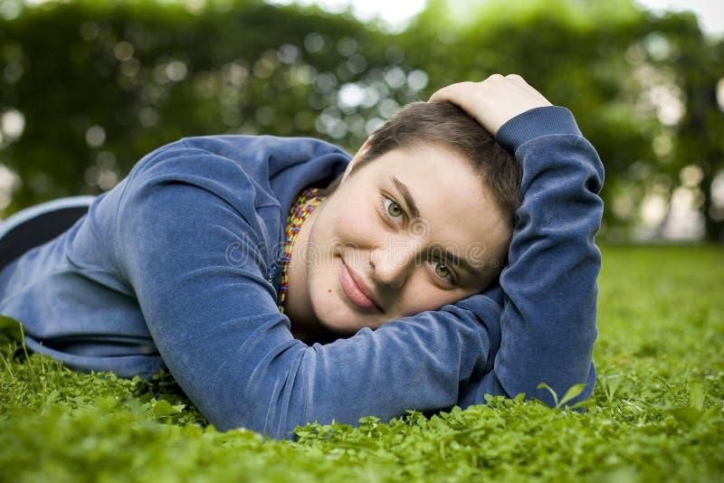 Портрет красивой девушки с короткими волосами и зелеными глазами лежит на траве, усмехаясь и смотря камеру стоковое изображение