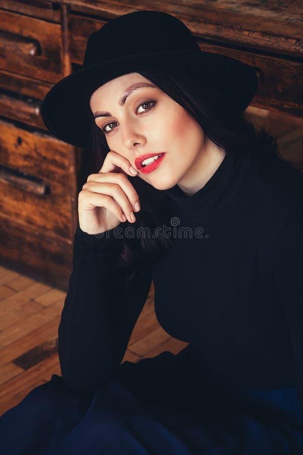 Портрет красивой женщины брюнета в шляпе на предпосылке деревянного стола Располагать женский портрет Взгляд стоковые фотографии rf
