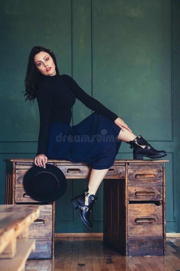 Портрет красивой женщины брюнета в шляпе на предпосылке деревянного стола Располагать женский портрет Взгляд стоковое изображение