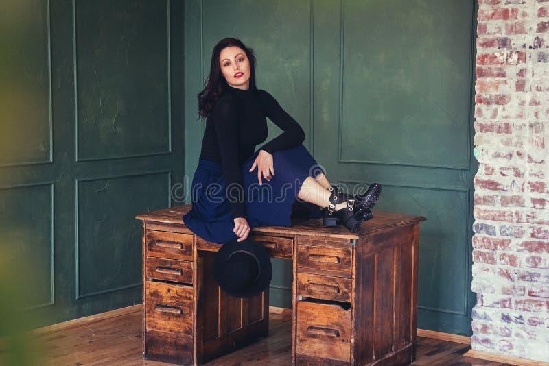 Портрет красивой женщины брюнета в шляпе на предпосылке деревянного стола Располагать женский портрет Взгляд стоковая фотография rf