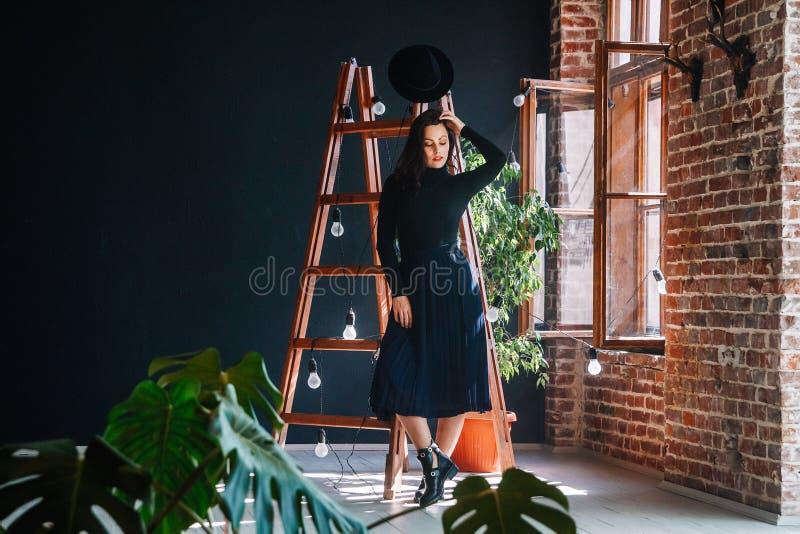 Портрет красивой женщины брюнета в шляпе на предпосылке деревянной лестницы Располагать женский портрет стоковая фотография