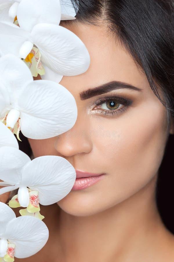 Портрет красивой женщины брюнета с белой орхидеей в ее руке стоковые изображения