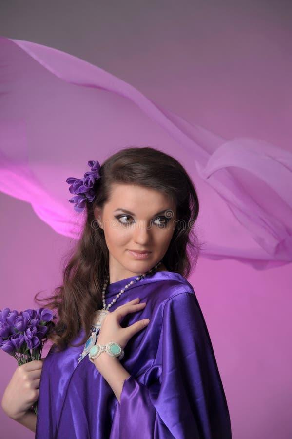 Портрет красивой женщины брюнета с восточным появлением у пурпурное платье, с шариками сделанными камней стоковая фотография