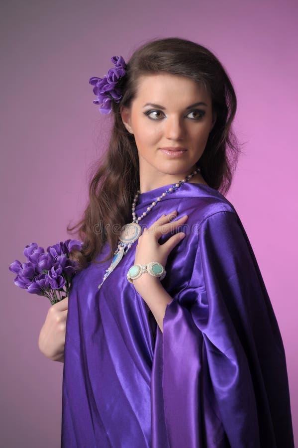 Портрет красивой женщины брюнета с восточным появлением у пурпурное платье, с шариками сделанными камней стоковые изображения