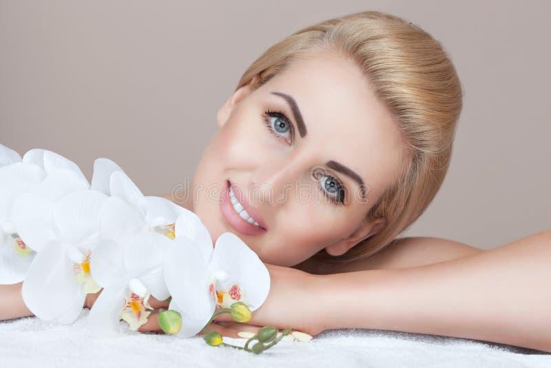 Портрет красивой женщины в салоне курорта с орхидеей в ее руке стоковые фотографии rf
