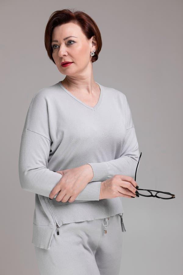 Портрет красивой женщины в светлых одеждах со стеклами в руке изолированной на светлой предпосылке стоковая фотография rf