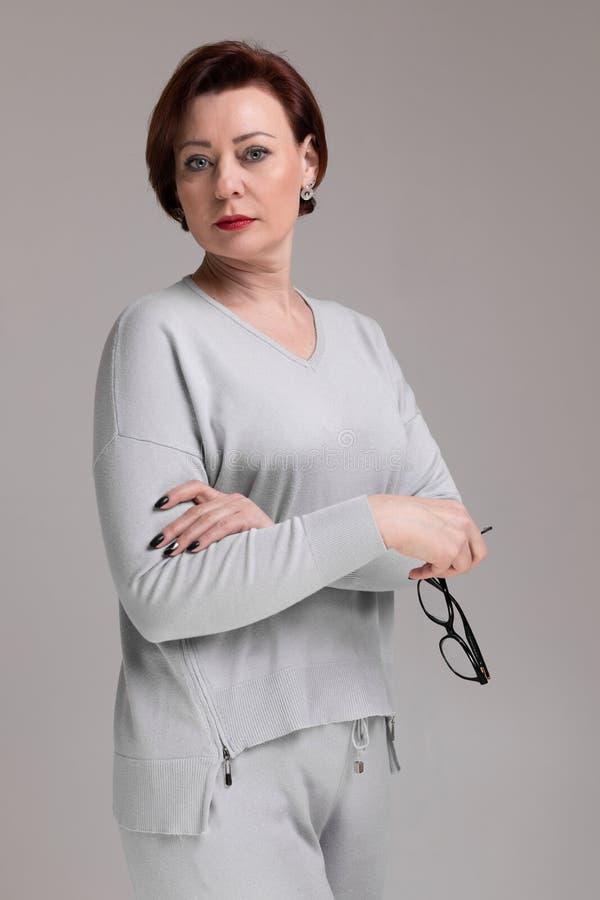 Портрет красивой женщины в светлых одеждах со стеклами в руке изолированной на светлой предпосылке стоковое изображение